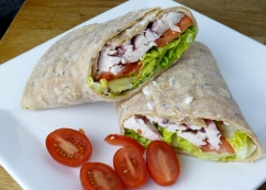GF Newburn Bakehouse seedy wrap with a spreading of mayo, shredded baby gen lettuce, sliced baby plumb tomatoes, sliced roasted chicken and a spoonful of cranberry sauce